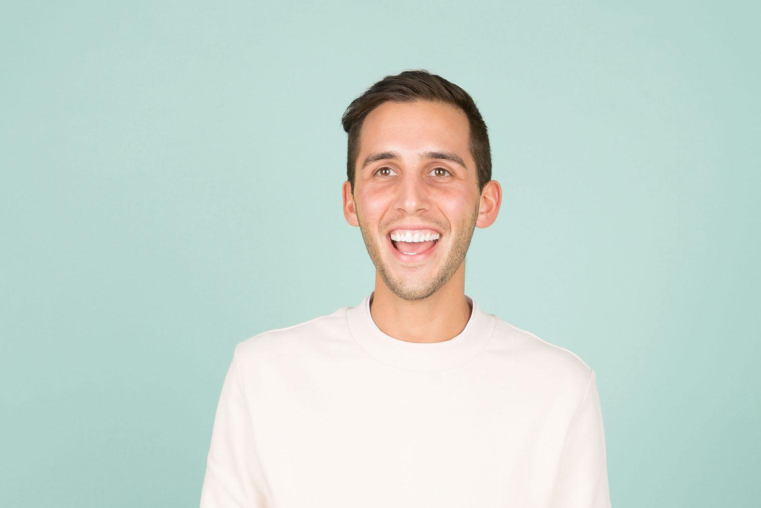 Mann i hvit genser som smiler