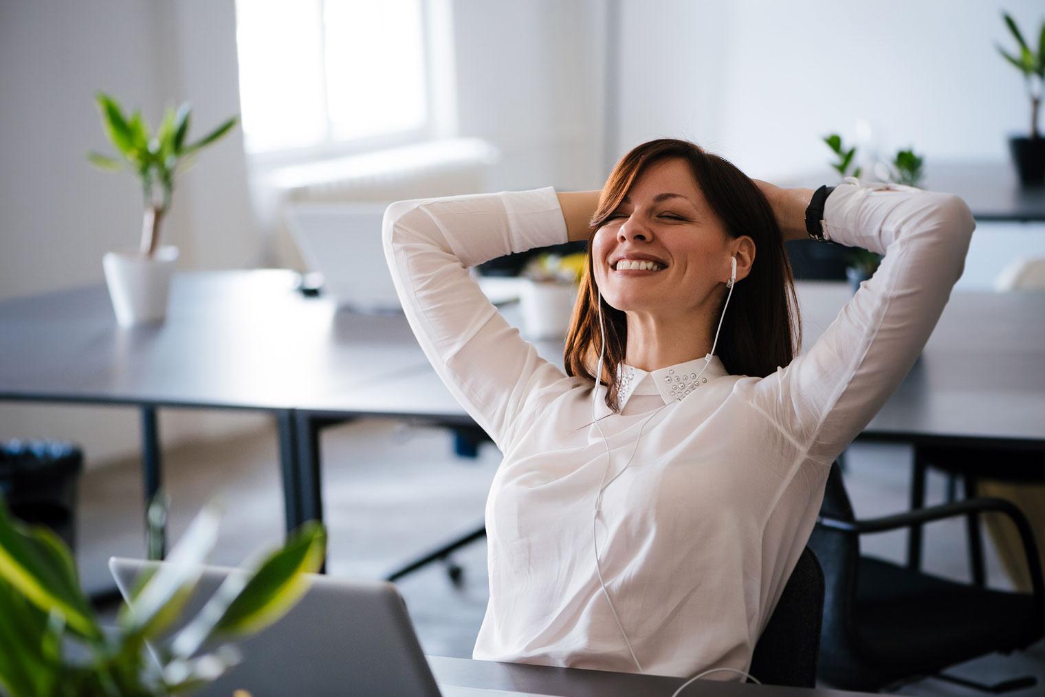 Smilende kvinne som lener seg tilbake i kontorstol