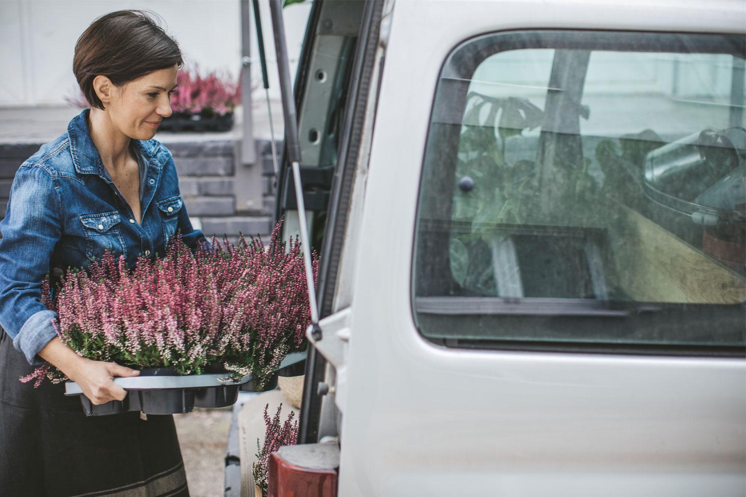 Kvinne som bærer planter inn i en bil