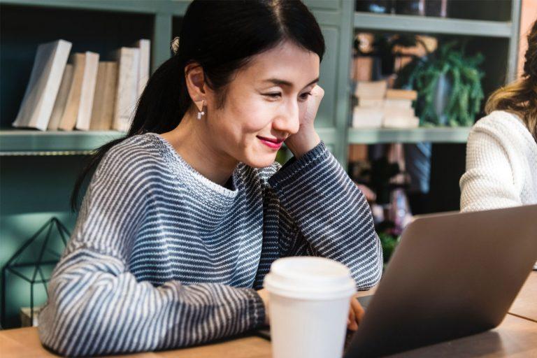 Kvinne som smiler og arbeider på en laptop