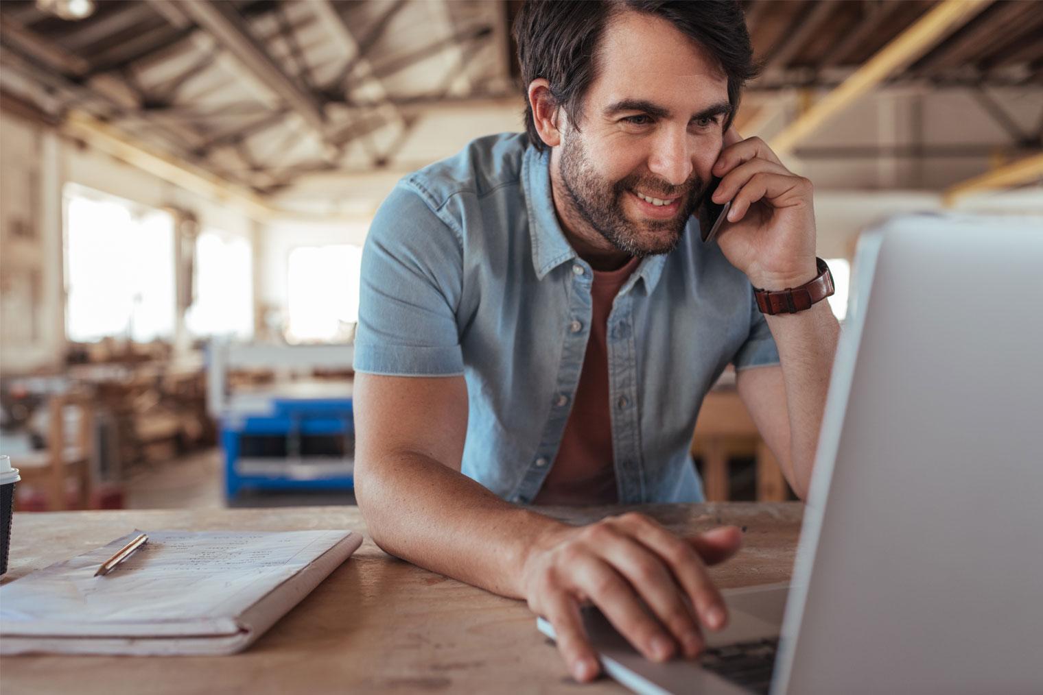 Mann med laptop på et verksted