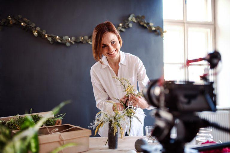 Kvinne som setter opp blomster og tar bilder
